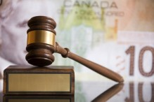 Wooden justice gavel and block with brass plate in front of a Canadian one hundred dollar bill.